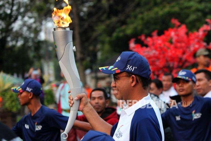 Gubernur DKI Jakarta Anies Baswedan membawa obor saat Torch Relay Asian Games 2018 di Balaikota, Jakarta, Rabu (15/8).