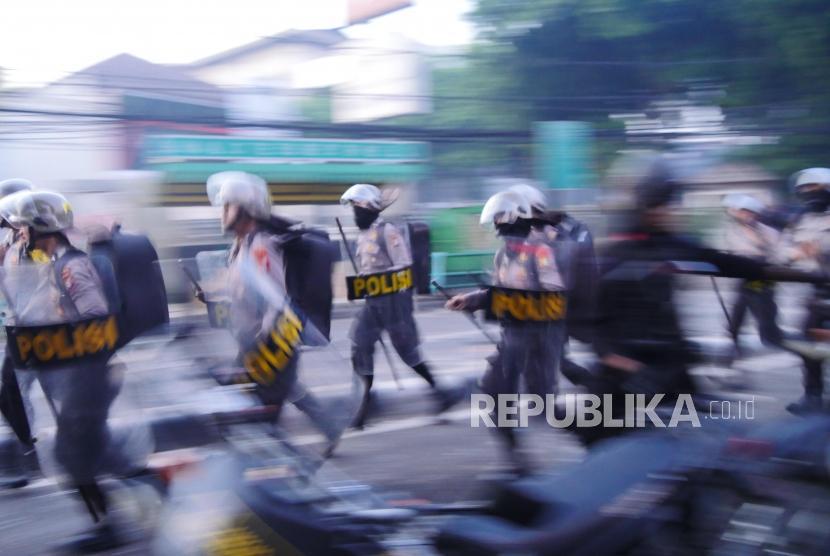 Petugas polisi berlari saat menuju lokasi massa di Jl KS Tubun, Petamburan, Jakarta, Rabu (22/5).