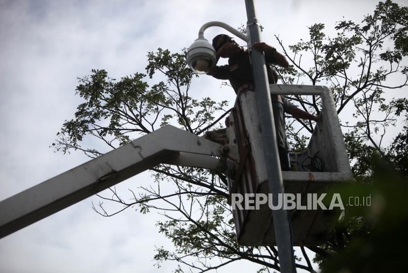 Petugas Dishub memasang CCTV ditiang persimpang Jalan Jatibaru, Tanah Abang, Jakarta, Jumat (9/2).