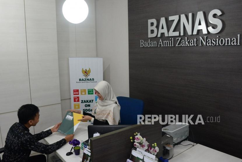 Petugas amil melayani muzaki di counter layanan muzaki Badan Amil Zakat Nasional (Baznas), Jakarta, Rabu (2/1).