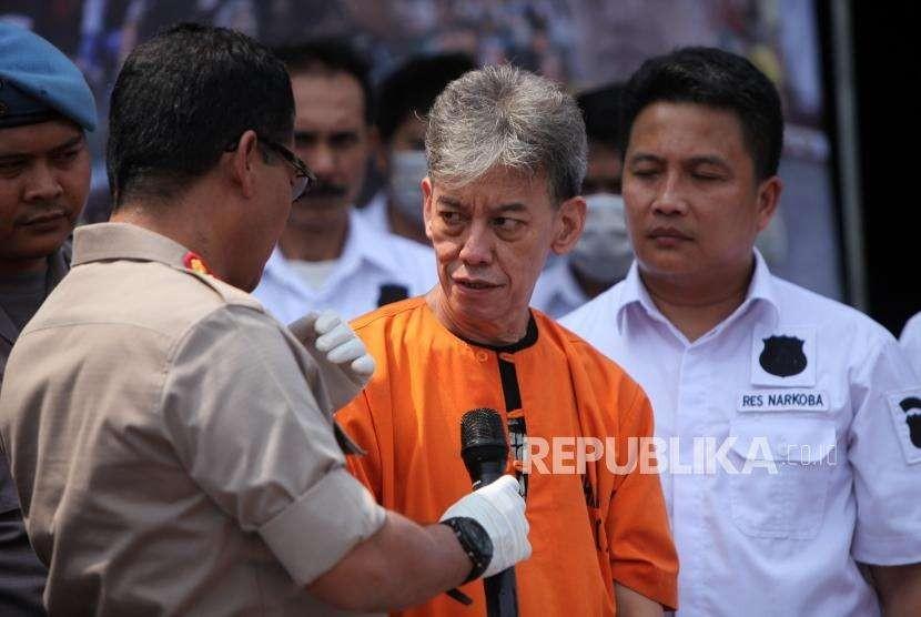 Kabid Humas Polda Metro Jaya Kombes Pol Argo Yuwono berbicang dengan tersangka Musisi Senior Fariz RM saat rilis kasus jaringan Narkoba yang melibatkan publik figur di Polres Jakarta Utara, Jakarta, Ahad (26/8).