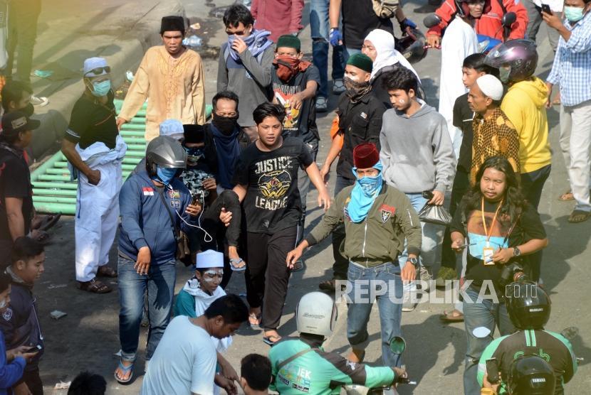 Sejumlah massa menggotong massa yang terluka saat terjadi kerusuhan di Jalan Jatibaru Raya, Tanah Abang, Jakarta, Rabu (22/5).