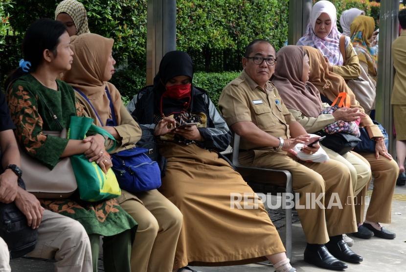 Sejumlah Aparatur Sipil Negara (ASN) menunggu bus pada jam pulang kerja di Jalan Medan Merdeka Selatan, Gambir, Jakarta, Senin (6/5).
