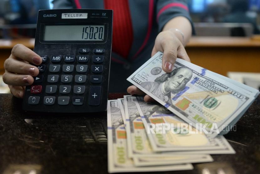 Petugas menghitung uang pecahan dolar Amerika Serikat di gerai penukaran mata uang asing. ilustrasi
