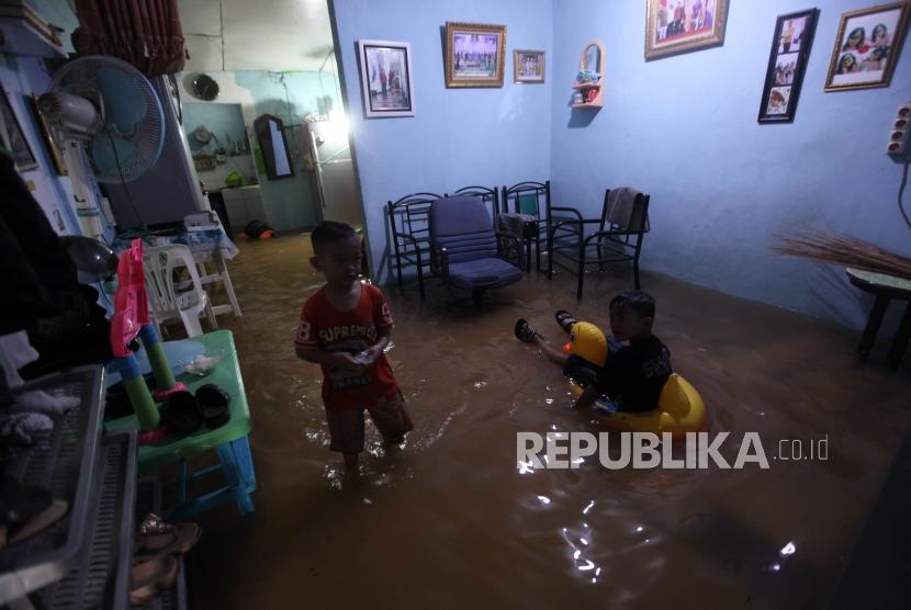 Sejumlah anak beraktivitas dirumahnya saat banjir akibat luapan Kali Ciliwung di Kebon Pala, Kampung Melayu, Jakarta, Senin (5/2).