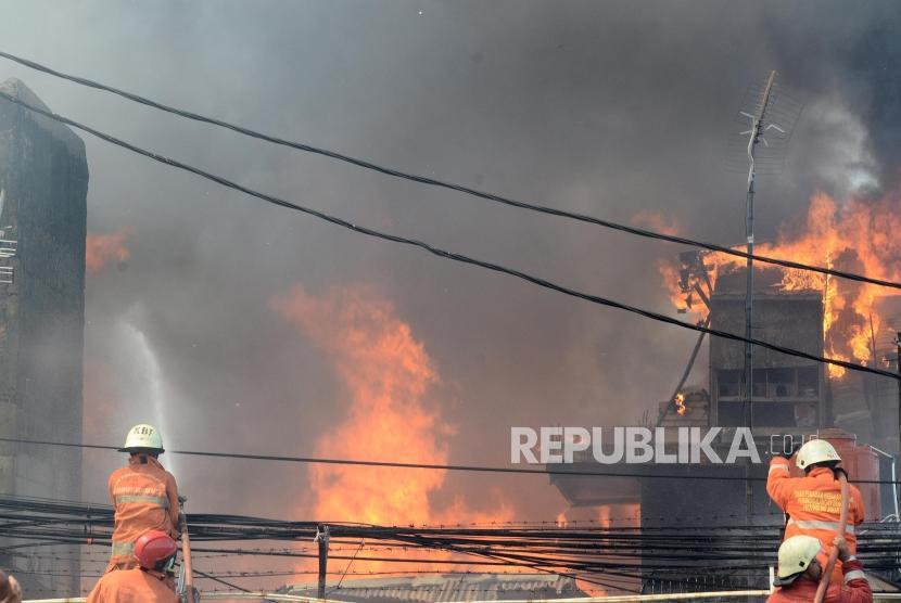 Kebakaran Pemukiman di Manggarai. Petugas pemadam kebakaran berusaha memadamkan api dari kebakaran yang terjadi di pemukiman padat penduduk di Jalan Lebak Swadaya I, Kampung Bali daerah Matraman, Jakarta, Rabu (10/7).