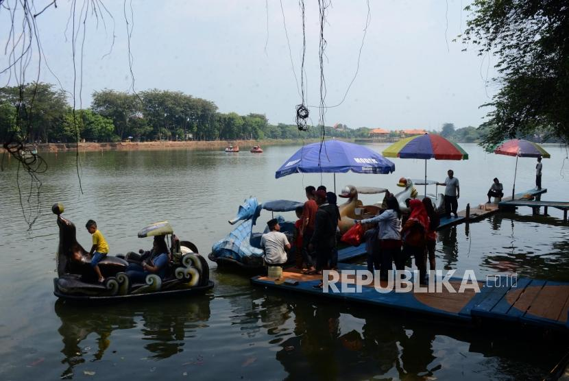 Sejumlah wisatawan mengantre menaiki perahu bebek di Setu Babakan, Jakarta, Ahad (9/6).
