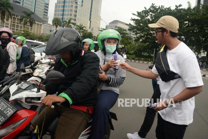 Relawan Millenial Jokowi-Amin melakukan aksi simpatik dengan membagikan coklat kepada pengendara di Kawasan Patung Kuda, Monas, Jakarta, Kamis (18/4).