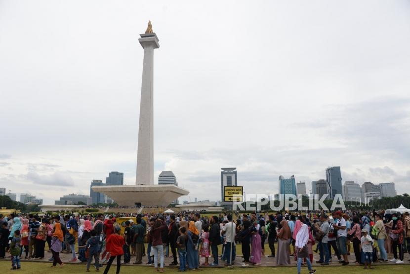 ejumlah warga mengantri untuk masuk ketugu monas, Jakarta, Selasa (1/1).