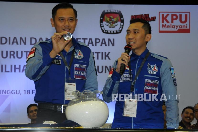 Komandan Satuan Tugas Bersama Partai Demokrat Agus Harimurti Yudhoyono (kiri) menunjukan bola nomor urut undian saat acara Pengundian Nomor Urut Peserta Pemilu 2019 di Kantor KPU, Jakarta, Ahad (18/2).
