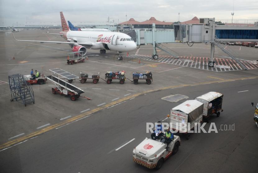 Petugas masukan barang milik penumpang ke bagasi pesawat di Bandara Internasional Soekarno,-Hatta, Tanggerang,Banten, Kamis (7/2).