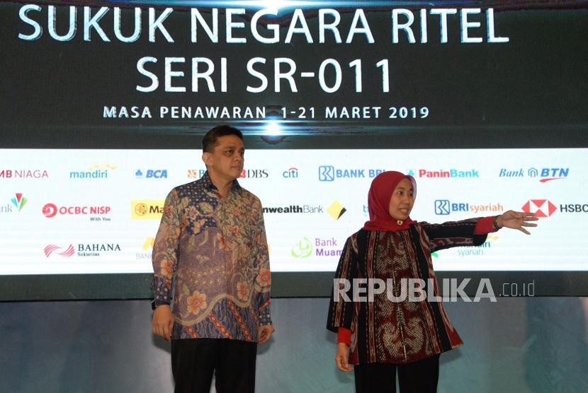 Direktur Jenderal Pengelolaan Pembiayaan dan Risiko Kementerian Keuangan Luky Alfirman (kiri) berbincang bersama Direktur Pembiayaan Syariah Direktorat Jenderal Pengelolaan Pembiayaan dan Risiko Kementerian Keuangan Dwi Irianti Hadiningdyah pada peluncuran Sukuk Negara Ritel Seri SR-011 di Jakarta, Jumat (1/3).