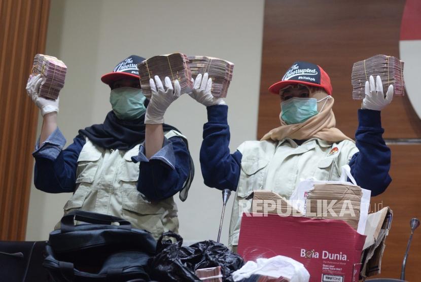 Petugas  KPK  menunjukan barang bukti operasi  tangkap tangan yang  dilakukan Komisi Pemberantasan Korupsi terhadap di Jakarta, Rabu (12/12).