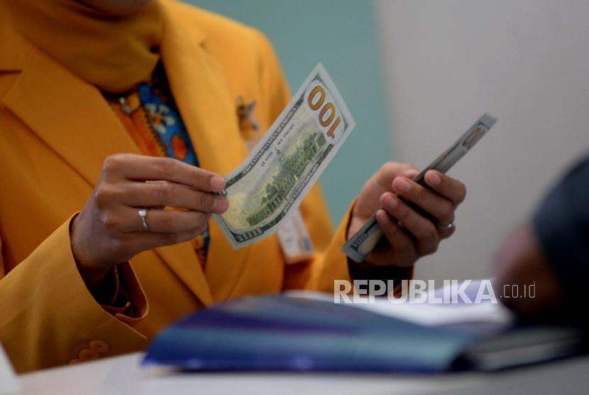 Petugas melayani nasabah ketika melakukan transaksi di bank