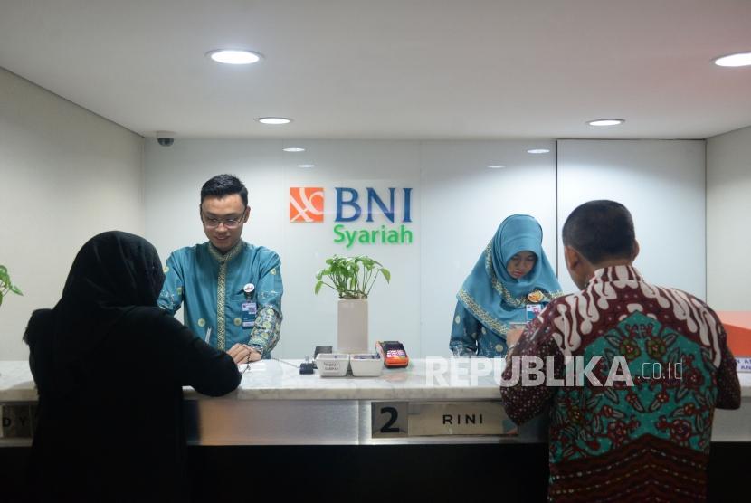 Petugas melayani transaksi nasabah di kantor layanan BNI Syariah, Jakarta,Kamis (1/2).