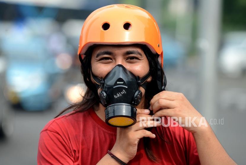Sejumlah aktivis Gerakan Inisiatif Bersihkan Udara Koalisi Semesta (Ibu Kota) mengenakan masker sebelum melaksanakan aksi di Bundaran HI, Jakarta, Rabu (5/12).