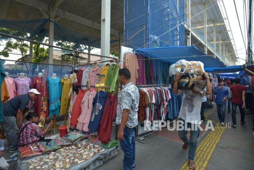 Warga melintas didekat barang dagangan para pedagang di Jalan Jatibaru, Tanah Abang, Jakarta, Kamis (27/9).