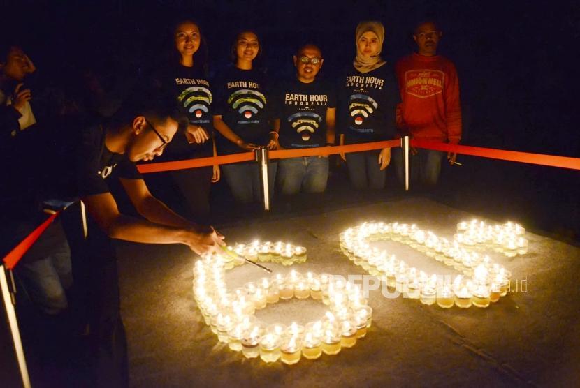 Sejumlah aktivis dari Eart Hour menyalakan lilin saat listrik dipadamkan pada acara gelaran tahunan Earth Hour 2018, di kawasan Gedung Sate, Kota Bandung, Ahad (25/3).