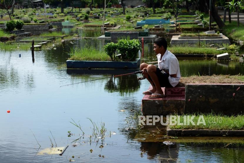 Anak-anak memancing ikan pada genangan air di Tempat Pemakaman Umum (TPU) Semper, Cilincing, Jakarta Utara, Rabu (5/12).