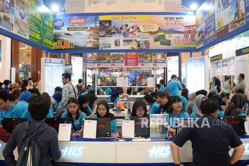 Pengunjung mencari info pemesanan tiket di salah satu stan pada Garuda Indonesia Travel Fair (GATF) phase II 2018 di Jakarta Convention Center, Jumat (5/10).