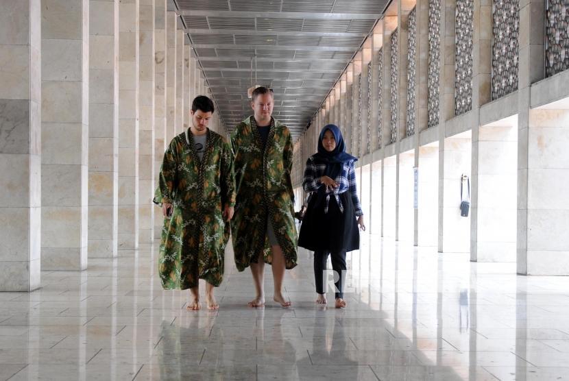 Pemandu wisata memberikan penjelasan kepada turis mancanegara di Masjid Istiqlal, Jakarta, Ahad (28/1).