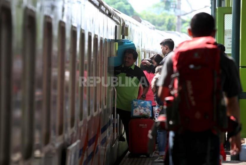 Porter membantu mengangkat barang bawaan calon penumpang kereta api (ILUSTRASI).