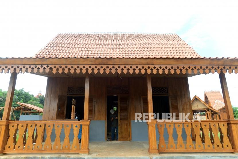 Pekerja menyelesaikan pembangunan Kampung Budaya Betawi di Setu Babakan, Jakarta, Kamis (14/3).