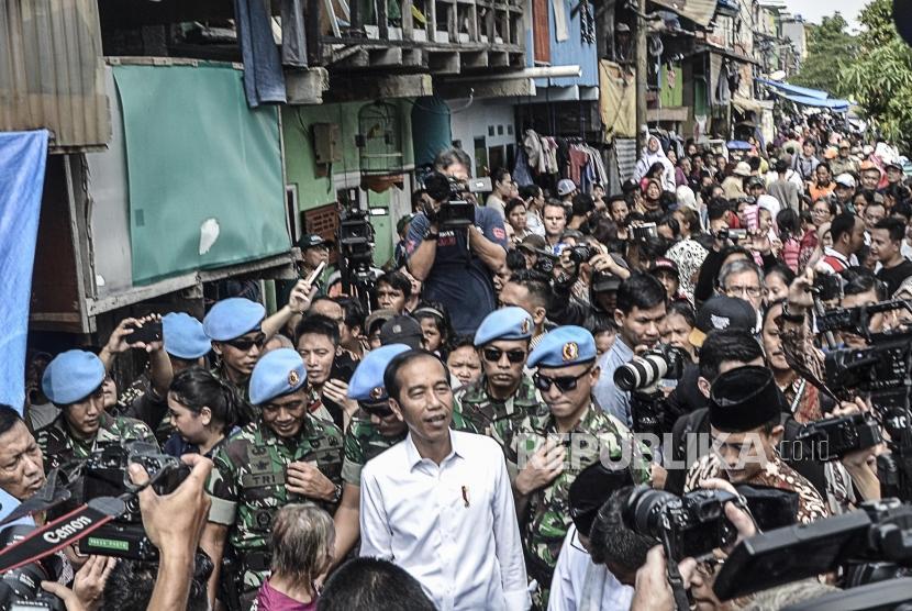 Capres Petahana Joko Widodo (tengah) menyapa warga usai pidato kemenangan sebagai Presiden periode 2019-2024 di Kampung deret,Tanah tinggi,Johor baru, Jakarta Pusat, Selasa (21/5).
