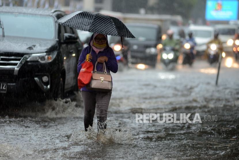 Warga melintasi genangan air di kawasan Pancoran, Jakarta (ilustrasi)