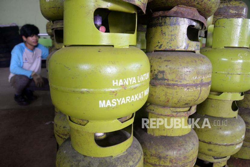 Pekerja menata tabung gas tiga kilogram di agen elpiji di kawasan Mampang Prapatan,Jakarta, Selasa (20/2).