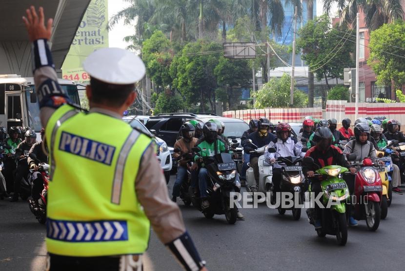 Polisi mengatur lalu lintas saat uji coba perluasan ganjil-genap di kawasan Pancoran, Jakarta Selatan, Senin (2/7).