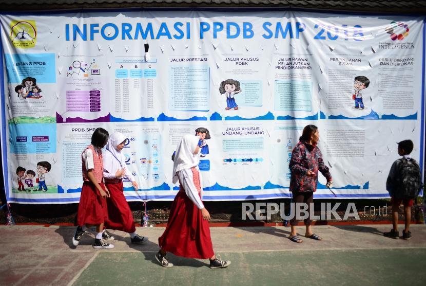 PPDB Kota Bandung. Siswa berseragam sekolah dasar melintasi baliho informasi Perimaan Peserta Didik Baru (PPDB) di SMPN 34 Bandung, Senin (2/7).