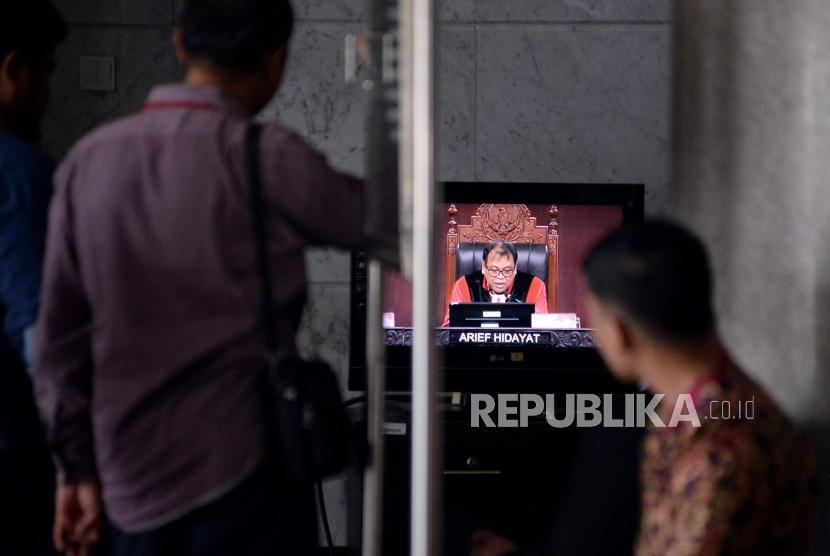 Pengunjung menagmati layar televisi ketika Ketua Majelis Hakim Mahkamah Konstitusi (MK) Arief Hidayat saat memimpin jalannya sidang uji materi Undang-Undang Nomor 7 Tahun 2017 tentang Pemilihan Umum (UU Pemilu) dengan agenda pembacaan putusan di Mahkamah Konstitusi, Jakarta, Kamis (11/1).