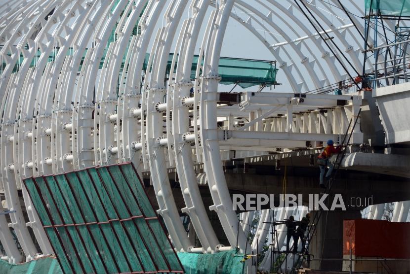 Sejumlah pekerja menyelesaikan pembangunan stasiun Kereta Light Rail Transit (LRT) di Jakarta, Jumat (4/1).
