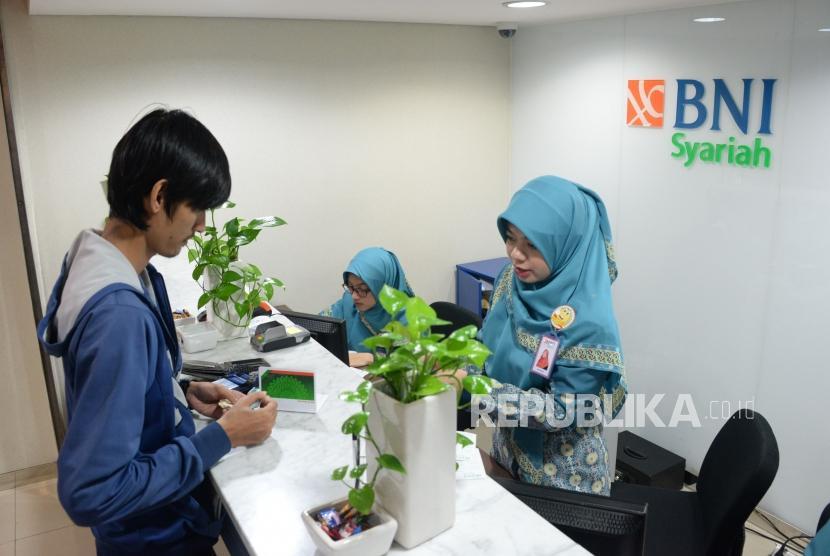 Karyawan melayani transaksi nasabah di kantor layanan BNI Syariah, Jakarta, Selasa (22/1).