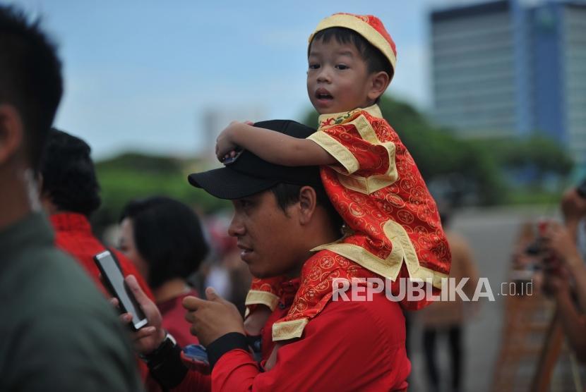Seorang anak digendong orang tuanya saat menghadiri Perayaan Imlek Nasional 2019 di JI Expo Kemayoran, Jakarta, Kamis (7/2).