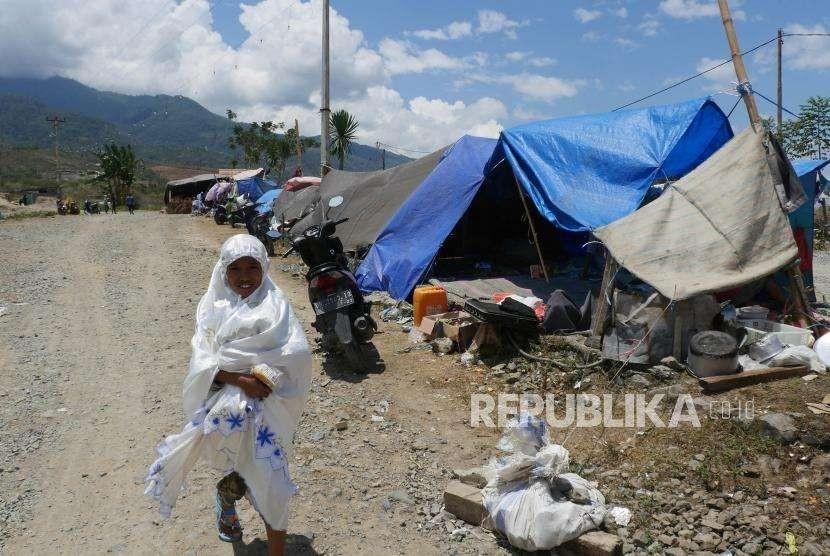Seorang anak melintas dijejeran tenda pengungsian di tempat pengungsian Duyu, Palu Barat, kecamatan Tatanga, Selasa (9/10).