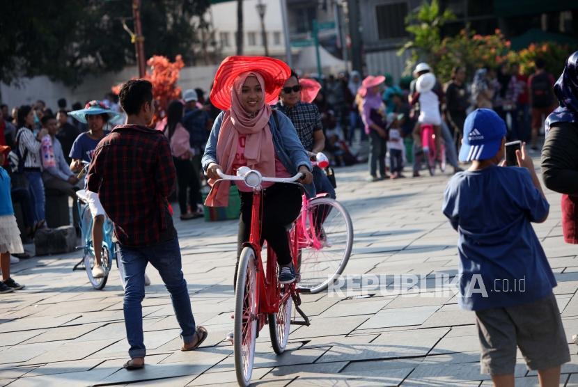 Pengunjung bermain sepeda di Taman Fatahillah, Kota Tua, Jakarta, Selasa (1/5).