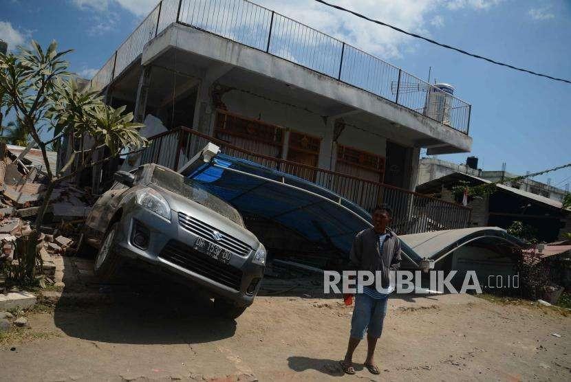 Warga  berada di depan mobil dan rumah yang rusak  akibat gempa, Desa Pemenang, Lombok Utara, NTB, Rabu (8/8).