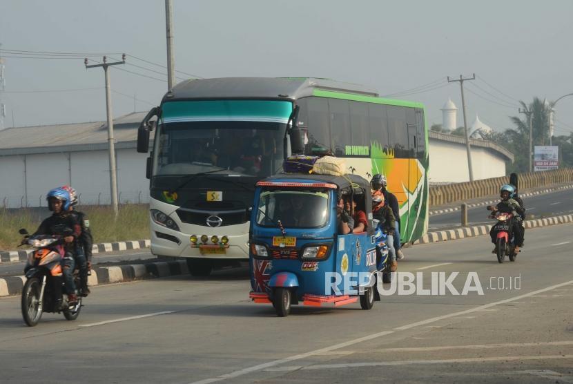 Pemudik mengunakan bajaj melintasi kawasan jalur mudik fly over lamaran, Karawang, Jawa Barat, Ahad (10/6).
