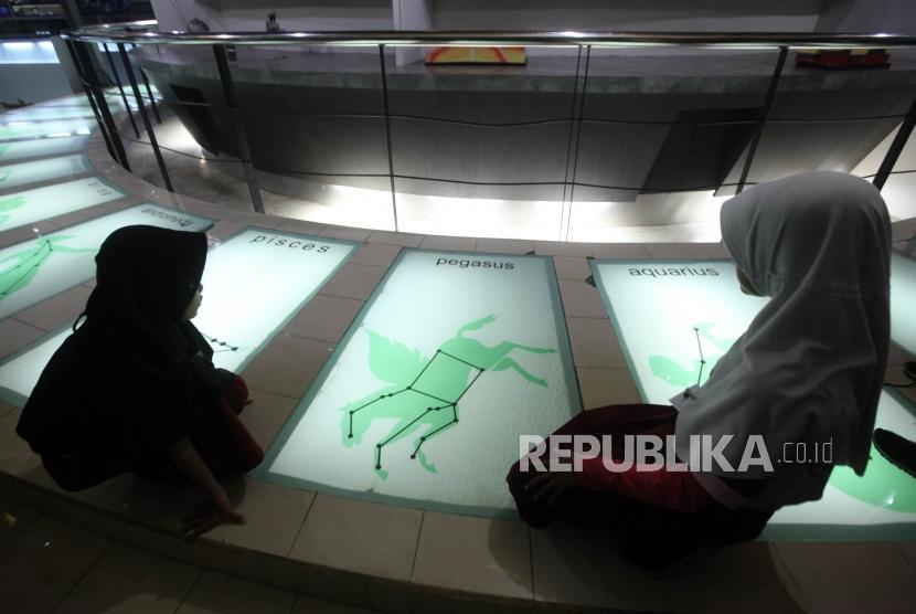 Sejumlah siswa Sekolah Dasar Peninggalan 04 Ciledug Tangerang (SD) mengamati rasi bintang tata surya saat berkunjung ke Planetarium Jakarta, Kamis (8/11).