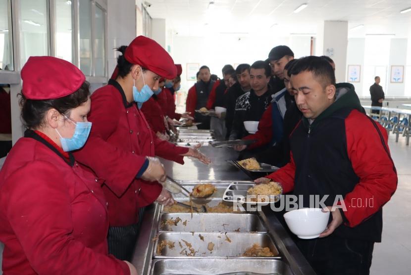 Para peserta didik kamp pendidikan vokasi etnis Uighur di Kota Kashgar, Daerah Otonomi Xinjiang, Cina, antre makan siang di kantin saat jam istirahat, Jumat (3/1/2019).