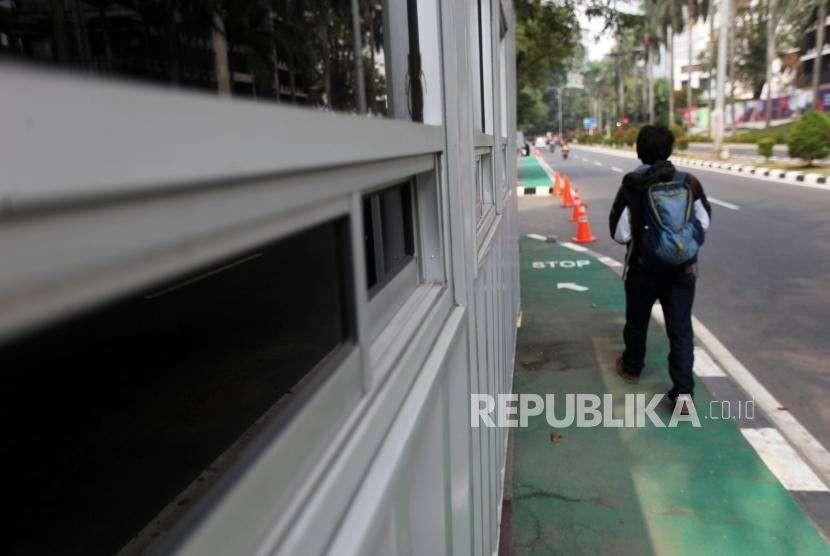 Warga melintas di samping kontainer tiket Asian Games 2018 yang berdiri di sepanjang trotoar Jalan Pintu Satu GBK, Kawasan Senayan, Jakarta, Selasa (7/8).