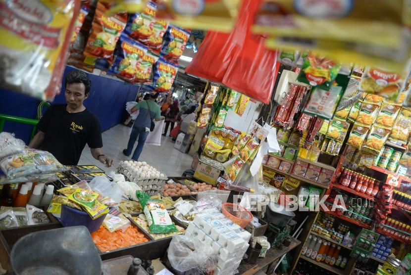 Pedagang melayani pembeli di kios sembako.