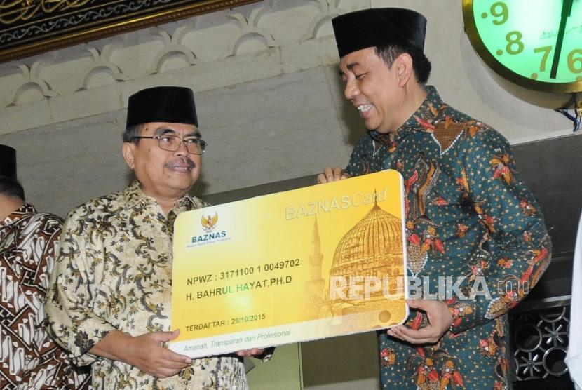Ketua Baznas Bambang Sudibyo (kiri) memberikan NPWZ kepada Wakil Ketua Badan Pelaksana Pengelola Masjid Istiqlal Bahrul Hayat (kanan) pada Peresmian Unit Pengelola Zakat (UPZ) Baznas Masjid Istiqlal di Masjid Istiqlal, Jakarta (17/5).
