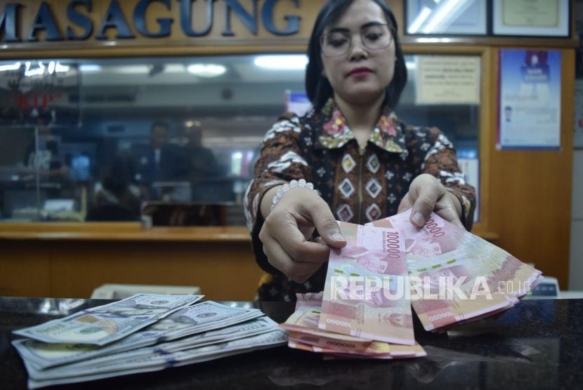 Petugas menghitung mata uang rupiah dan dolar AS di salah satu tempat penukaran uang di Jakarta, Jumat (9/11).