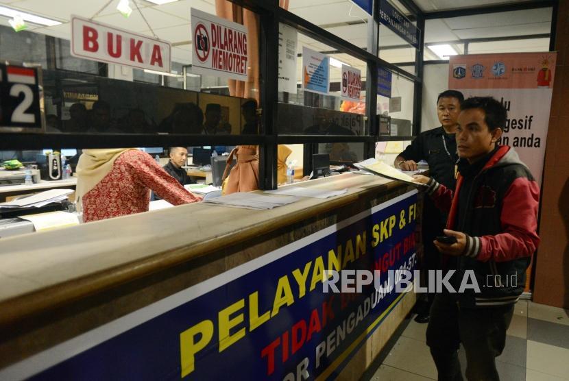 Warga menyelesaikan pembayaran pajak kendaraan bermotor di Kantor Samsat Polda Metro Jaya, Jakarta, Jumat (16/11).