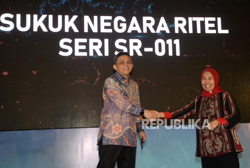 Direktur Jenderal Pengelolaan Pembiayaan dan Risiko Kementerian Keuangan Luky Alfirman (kiri) berjabat tangan dengan Direktur Pembiayaan Syariah Direktorat Jenderal Pengelolaan Pembiayaan dan Risiko Kementerian Keuangan Dwi Irianti Hadiningdyah pada peluncuran Sukuk Negara Ritel Seri SR-011 di Jakarta, Jumat (1/3).