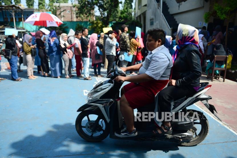 PPDB Kota Bandung. Seorang siswa berseragam sekolah dasar mengendarai sepeda motor melintasi antrean Perimaan Peserta Didik Baru (PPDB) di SMPN 34 Bandung, Senin (2/7).