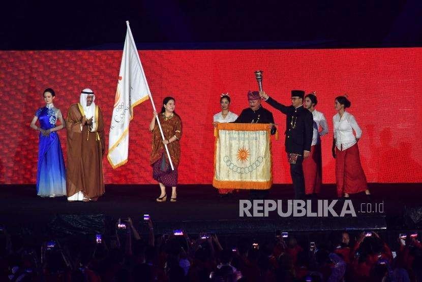 Gubernur DKI Jakarta, Anies Baswedan (kanan) bersiap memberikan obor pertama Penyelanggaraan Asian Games  pada penutupan Asian Games ke 18 di Stadion Utama Gelota Bung Karno, Jakarta, Ahad(2/9).